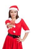 Asiatisk julflicka med Santa Claus kläder och den röda gåvaasken Fotografering för Bildbyråer