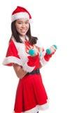 Asiatisk julflicka med Santa Claus kläder och röda hantlar Arkivbild
