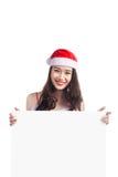 Asiatisk julflicka med Santa Claus kläder som rymmer det tomma tecknet Arkivfoto
