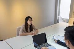 Asiatisk kandidat som omkring ser i intervjun Arkivfoto