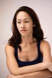 Asiatisk kinesisk damkänsla som är ledsen och ner ser Royaltyfri Bild