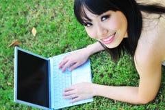asiatisk kinesisk flickabärbar dator som ler sött genom att använda royaltyfri foto