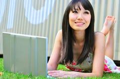asiatisk kinesisk flickabärbar dator som tänker genom att använda royaltyfri foto