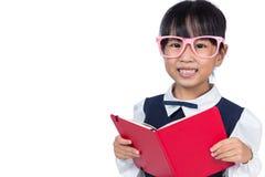 Asiatisk kinesisk grundskola för barn mellan 5 och 11 årflicka i enhetlig läsebok Arkivfoto