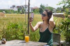 Asiatisk kinesisk kvinna på hennes 20-tal eller 30-tal som ler ha den roliga användande internet på mobiltelefonskytteselfie elle Arkivbilder
