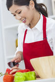 Asiatisk kinesisk kvinna som förbereder grönsaksalladmat i kök Arkivfoton