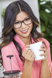 Asiatisk kinesisk kvinnaflicka i kök som dricker kaffe Arkivbilder