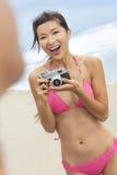 Asiatisk kinesisk kvinnaflickakamera på stranden i bikini Arkivbild