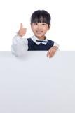 Asiatisk kinesisk liten flicka bak ett tomt vitt bräde arkivfoto