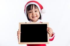 Asiatisk kinesisk liten flicka i meddelande för mellanrum för santa dräktinnehav Arkivfoto