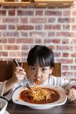 Asiatisk kinesisk liten flicka som äter spagetti bolognese Royaltyfria Bilder