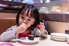 Asiatisk kinesisk liten flicka som äter sushi på en japansk restaurang royaltyfri bild