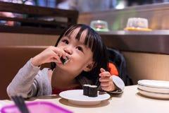 Asiatisk kinesisk liten flicka som äter sushi på en japansk restaurang royaltyfria bilder