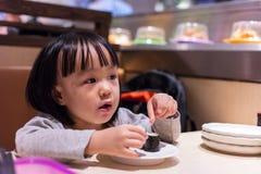 Asiatisk kinesisk liten flicka som äter sushi på en japansk restaurang arkivfoto