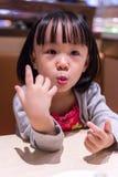 Asiatisk kinesisk liten flicka som äter sushi på en japansk restaurang fotografering för bildbyråer
