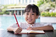 Asiatisk kinesisk liten flicka som gör läxa Arkivfoto