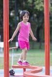 Asiatisk kinesisk liten flicka som g?r p? balansbommen arkivfoto