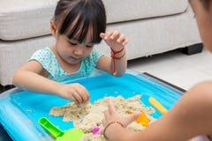 Asiatisk kinesisk liten flicka som hemma spelar kinetisk sand arkivbilder