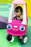 Asiatisk kinesisk liten flicka som kör leksakbilen fotografering för bildbyråer