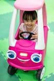 Asiatisk kinesisk liten flicka som kör leksakbilen arkivfoton