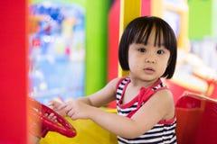 Asiatisk kinesisk liten flicka som kör Toy Bus Royaltyfri Fotografi