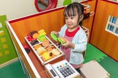 Asiatisk kinesisk liten flicka som roll-spelar på hamburgarelagret arkivbild