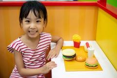 Asiatisk kinesisk liten flicka som roll-spelar på hamburgarelagret arkivbilder