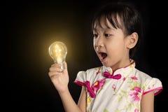 Asiatisk kinesisk liten flicka som rymmer en ljus kula royaltyfri bild
