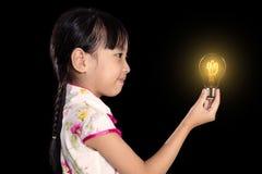 Asiatisk kinesisk liten flicka som rymmer en ljus kula arkivbild