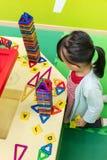 Asiatisk kinesisk liten flicka som spelar färgrika magnetplast-kvarter Royaltyfri Fotografi