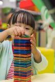 Asiatisk kinesisk liten flicka som spelar färgrika magnetplast-kvarter Arkivbild