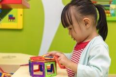 Asiatisk kinesisk liten flicka som spelar färgrika magnetplast-kvarter Arkivbilder