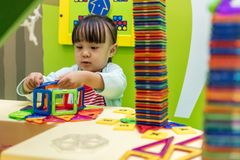 Asiatisk kinesisk liten flicka som spelar färgrika magnetplast-kvarter Fotografering för Bildbyråer