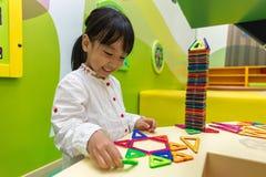 Asiatisk kinesisk liten flicka som spelar färgrika magnetplast-kvarter Royaltyfri Foto