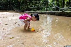 Asiatisk kinesisk liten flicka som spelar leksakfartyget på liten vik royaltyfria foton