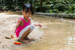 Asiatisk kinesisk liten flicka som spelar leksakfartyget på liten vik arkivbilder