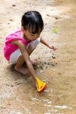 Asiatisk kinesisk liten flicka som spelar leksakfartyget på liten vik royaltyfria bilder