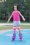 Asiatisk kinesisk liten flicka som spelar med rullskridskor arkivbild