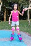 Asiatisk kinesisk liten flicka som spelar med rullskridskor arkivbilder
