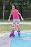 Asiatisk kinesisk liten flicka som spelar med rullskridskor royaltyfria bilder