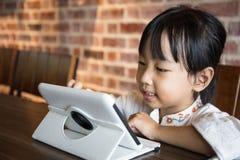 Asiatisk kinesisk liten flicka som spelar minnestavladatoren Royaltyfri Bild