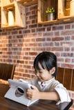 Asiatisk kinesisk liten flicka som spelar minnestavladatoren Arkivbild