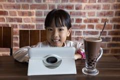 Asiatisk kinesisk liten flicka som spelar minnestavladatoren Royaltyfri Fotografi