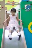 Asiatisk kinesisk liten flicka som spelar på glidbanan arkivfoto