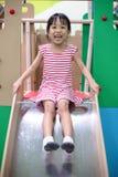 Asiatisk kinesisk liten flicka som spelar på glidbanan royaltyfri fotografi