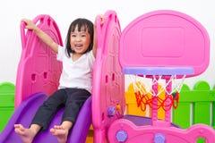 Asiatisk kinesisk liten flicka som spelar på glidbanan Royaltyfri Foto