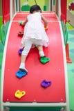 Asiatisk kinesisk liten flicka som spelar på kortkortet för att vagga den klättra väggen royaltyfria foton