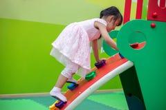 Asiatisk kinesisk liten flicka som spelar på kortkortet för att vagga den klättra väggen fotografering för bildbyråer