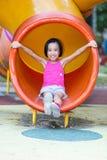 Asiatisk kinesisk liten flicka som spelar p? den utomhus- lekplatsen royaltyfria bilder