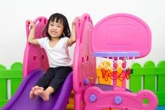 Asiatisk kinesisk liten flicka som spelar på glidbanan Royaltyfri Bild